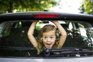 Little girl looking through glass of back car window