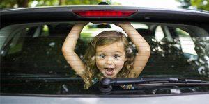 little girl looking through back car window