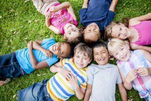 Smiling Kids Laying in Grass