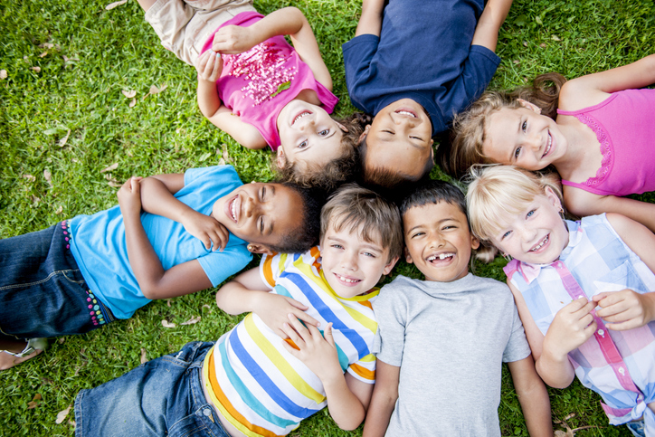 Smiling Kids Laying in Grass