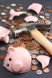 sad shattered piggy bank surrounded by money