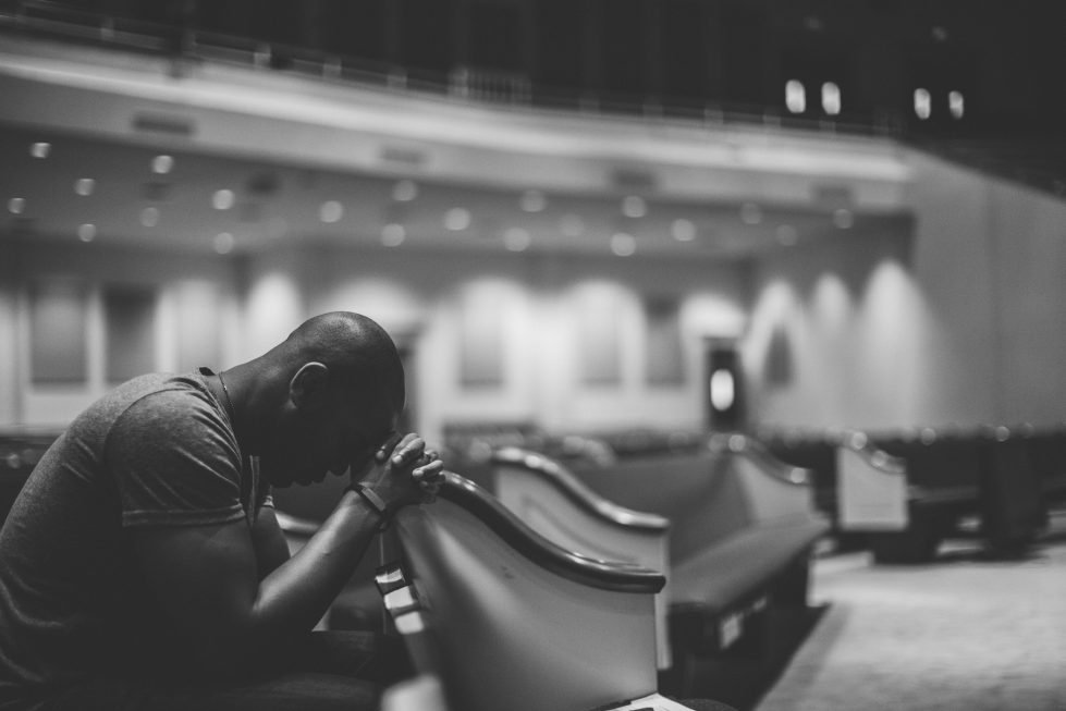Man praying in pew