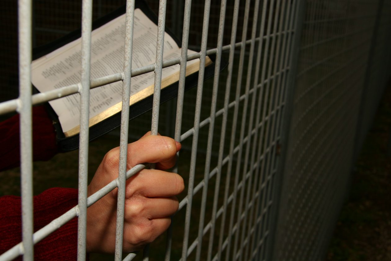Christian holding a Bible behind bars