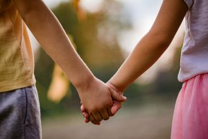 young girl and young boy holding hands