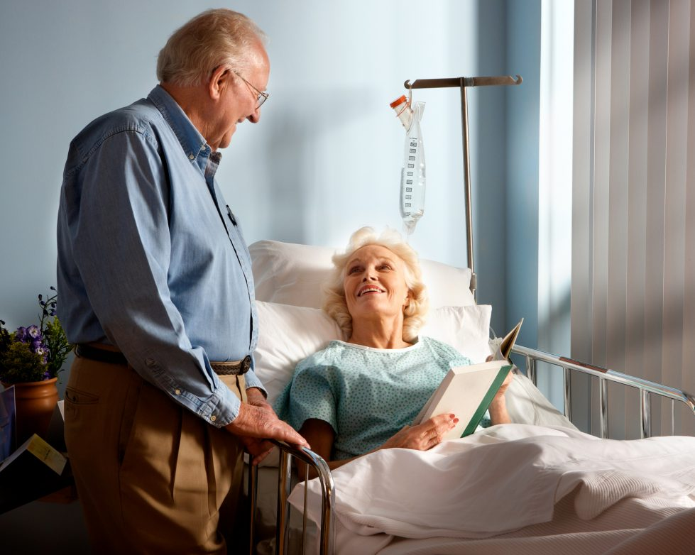 Old man beside wife's hospital bed